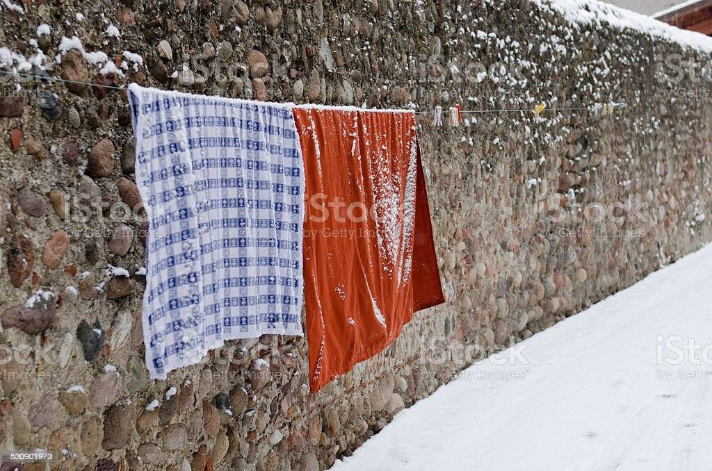 colorful wash clothes loundry dry rope winter snow stock photo