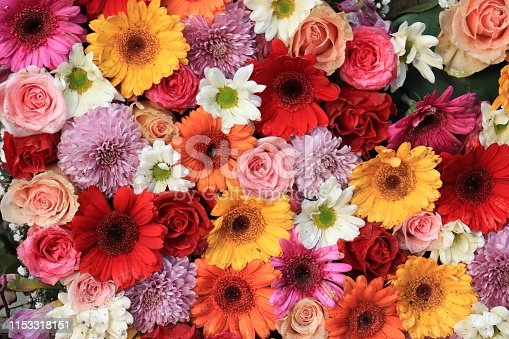 Mixed flower arrangement for a wedding: roses and gerberas in pink, yellow and red