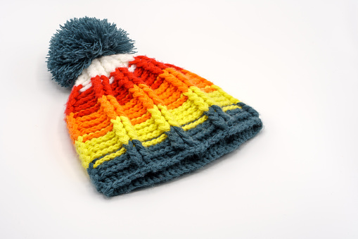 Colorful winter knitted hat on a white background.