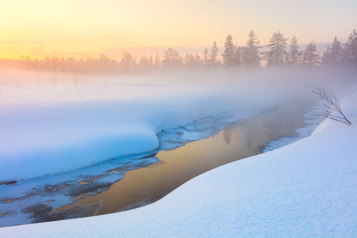 Colorful winter sunset in forest and river with beautiful misty fog, fantastic winter nature landscape