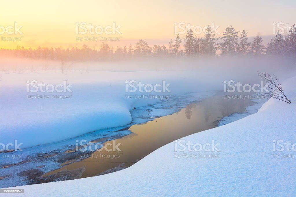 Colorful winter sunset in forest and river with beautiful misty stock photo