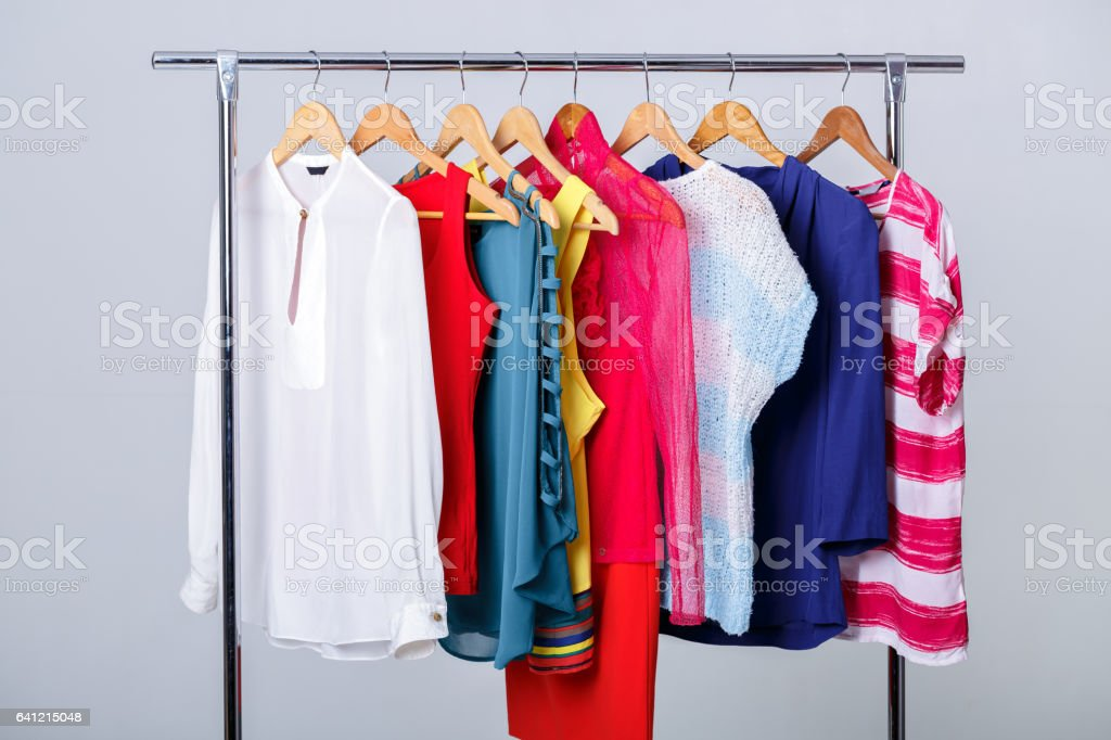 colorful womens clothes on hangers on rack on gray background. w stock photo