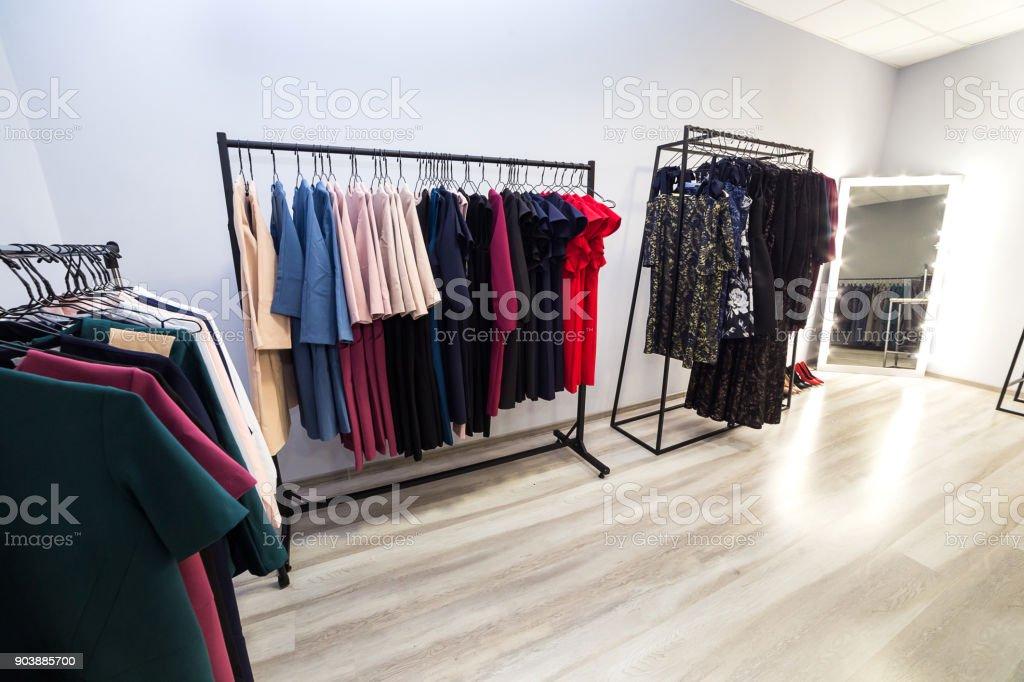 c88befa957a3fb kleurrijke vrouwen jurken en andere kleding op kleerhangers in een retail- winkel. Mode en