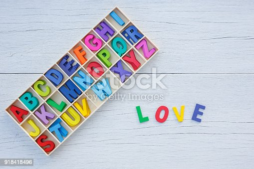 istock Colorful wooden alphabet in square box and LOVE word. Top view on white wooden 918418496