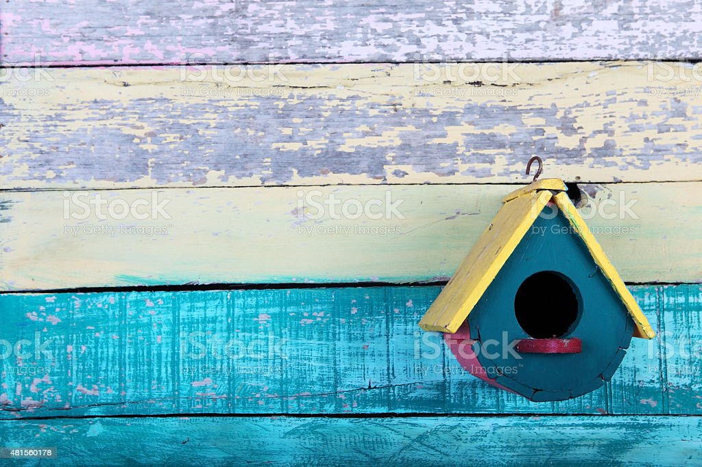 colorful wooden bird house with grunge background. stock photo