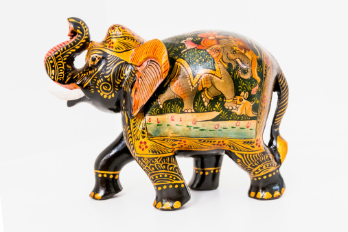 Colorful handmade and hand painted wooden elephant souvenir on white background.