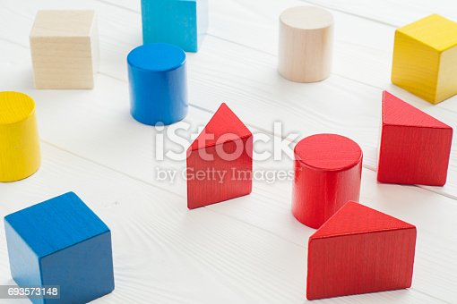 istock Colorful wooden geometric building blocks on white wooden background. 693573148