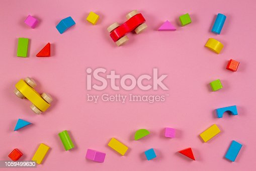 Colorful wooden toys and blocks on pink color background.