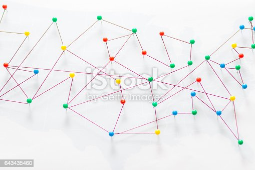 istock Colorful wool threads form a network between pins 643435460
