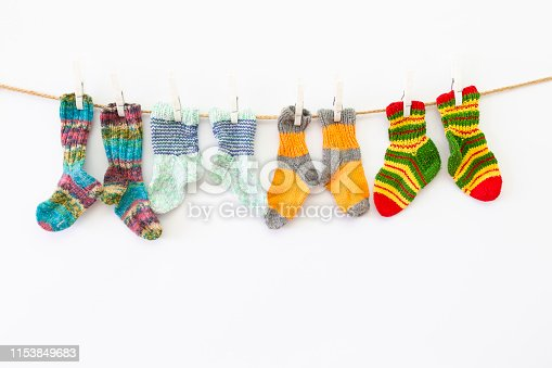 istock Colorful woolen socks on a rope on white background 1153849683