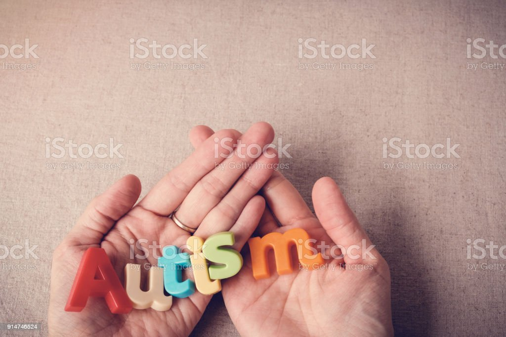 AUTISM colorful word on hands, wolrd Autism day, April Autism awareness month stock photo