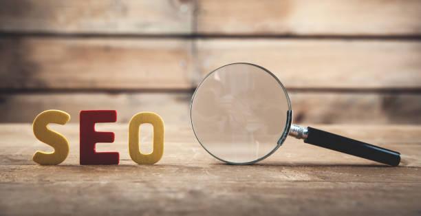 palabra colorida seo con lupa. optimización de motores de búsqueda - seo fotografías e imágenes de stock