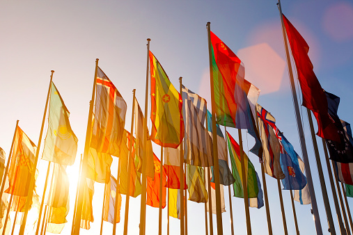 Group of many colorful internationl world flags waving in the sky at sunset, with shining sun and lens flare, low angle view.