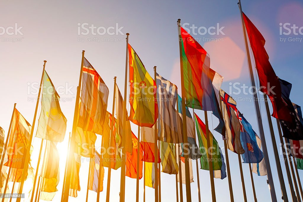Colorful world international flags waving in the sky at sunset stock photo