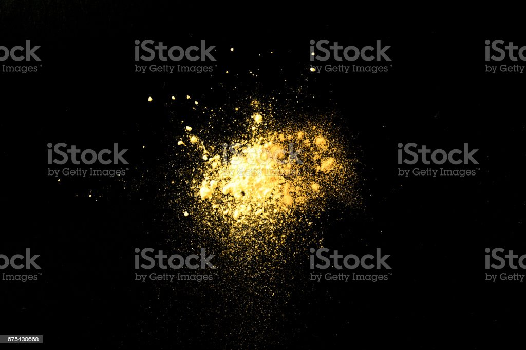 Splash of colorful yellow powder on a black background