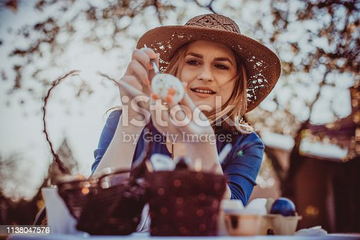 Woman celebrating Easter holiday and painting eggs outdoors on a beautiful sunny day