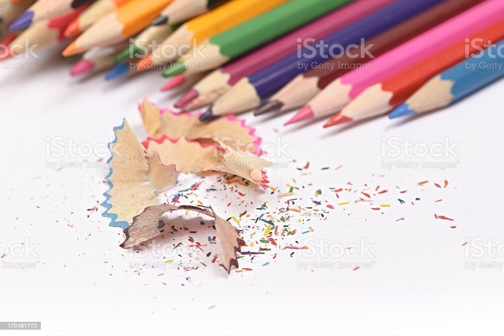 Coloring pencils and pencil shavings on white drawing paper royalty-free stock photo