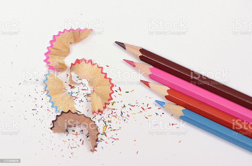 Coloring pencils and pencil shavings on white textured paper royalty-free stock photo