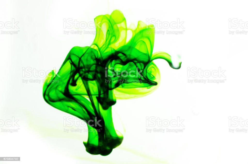 Colors dropped into liquid and photographed while in motion. Cloud of silky ink in water on white background royalty-free stock photo