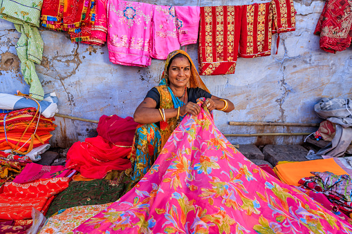 Indian woman selling colorful fabrics on local bazaar, Jodhpur, Rajasthan, India. Jodhpur is known as the Blue City due to the vivid blue-painted houses around the Mehrangarh Fort.