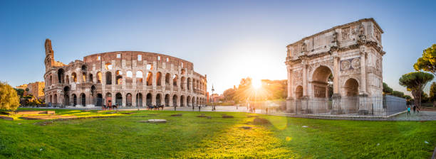 Colosseum and Constantine Arch at sunrise, Rome. Panorama Panoramic view of Colosseum and Constantine Arch at dawn, Rome, Italy coliseum rome stock pictures, royalty-free photos & images