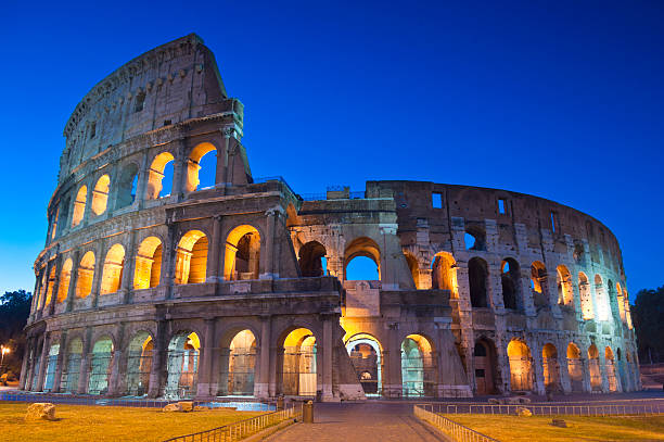 Colosseum, Colosseo, Rome Romes mighty Coliseum (AD 80), illuminated at night and icon of the city, still standing today as a testament to ancient engineering. palatine hill rome stock pictures, royalty-free photos & images