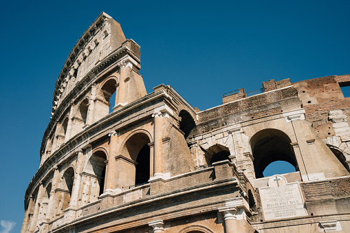 Colosseum in Rome from below. Italy travel destination. Blue sky in the background.