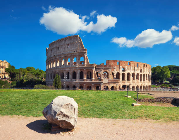 Colosseum in Rome, Italy, on a bright day Rome, Italy. View of Colosseum from the Palatine Hill on a sunny day with blue sky and clouds. palatine hill rome stock pictures, royalty-free photos & images