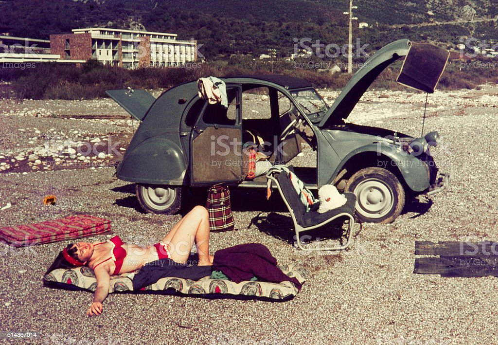 Colour slide from 1960s, young woman relaxing with her car. stock photo