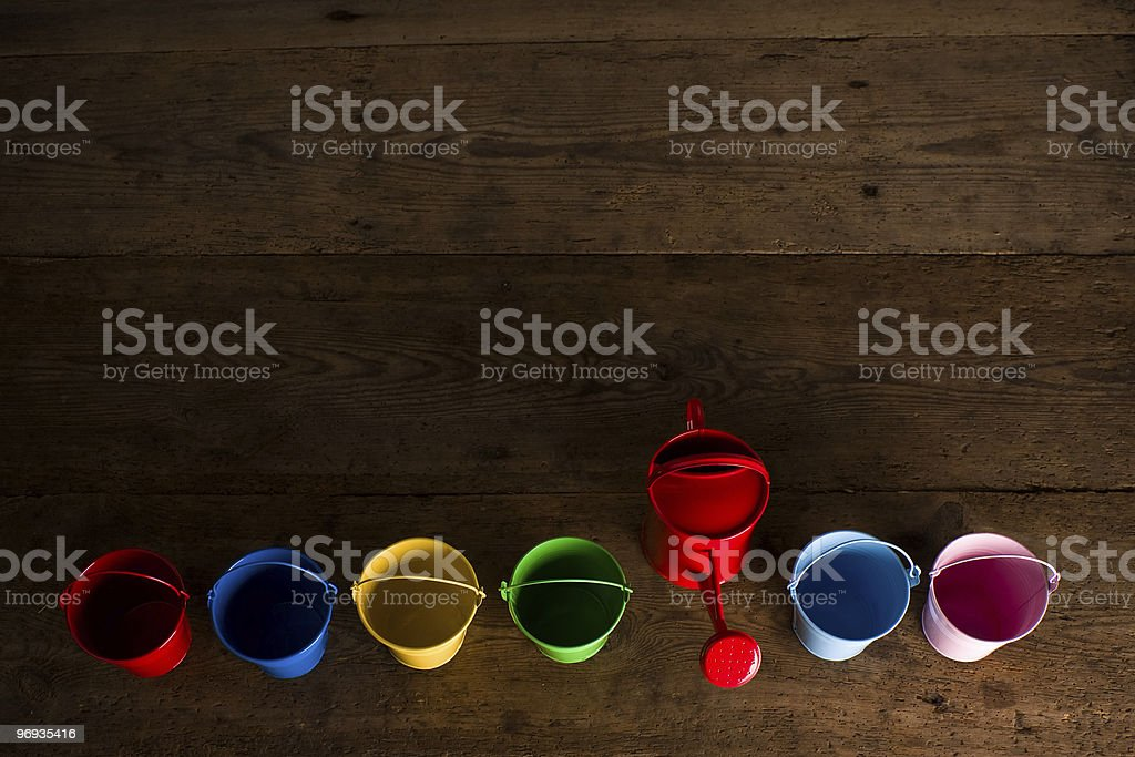 Coloured buckets and watering can in top view royalty-free stock photo