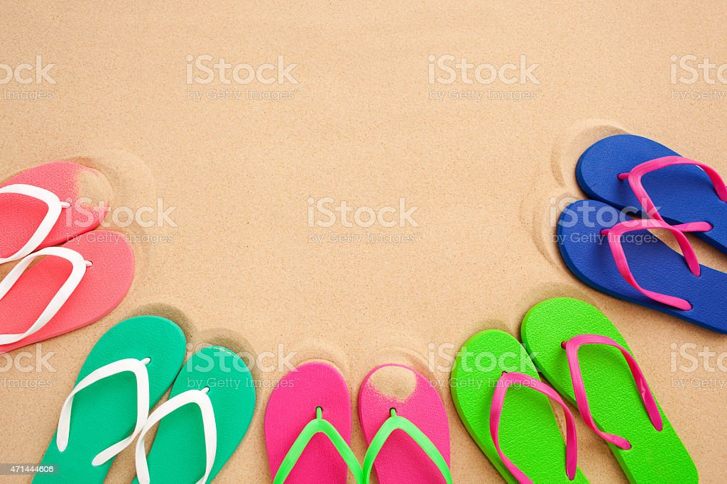 Flip flops on sandy beach. Coloured image with copy space.