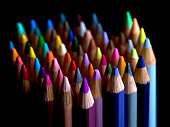 Brightly coloured pencils against a black backdrop