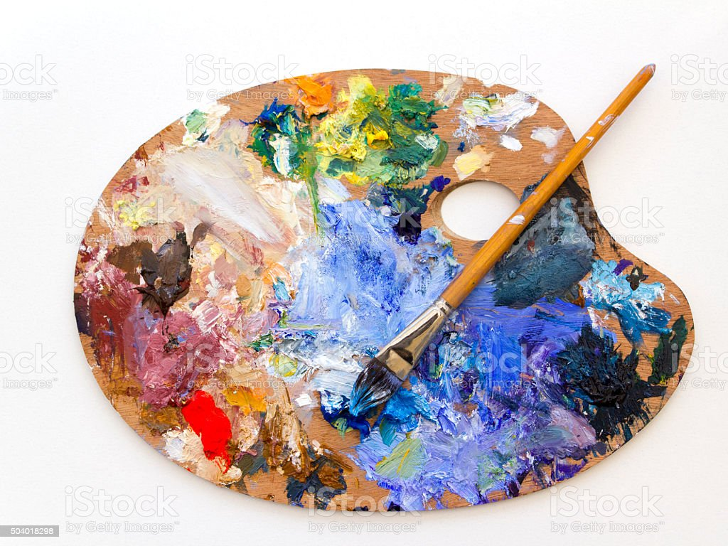 Colourful artists oil paint palette and brush on white stock photo
