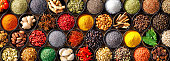 Colourful background from various herbs and spices for cooking in bowls. Top view