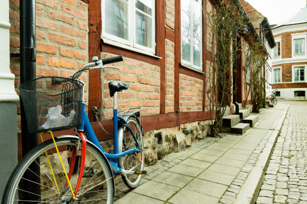 colourful bike standing against  a wall of an old half timberd house - lund stock photos and pictures