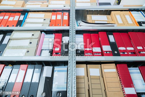 502086873 istock photo Colourful blank blind folders with files in the shelf. Archival, stacks of documents at the office or library. Physical document storage units 1150971187