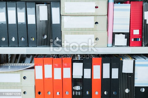 502086873 istock photo Colourful blank blind folders with files in the shelf. Archival, stacks of documents at the office or library. Physical document storage units 1150971225