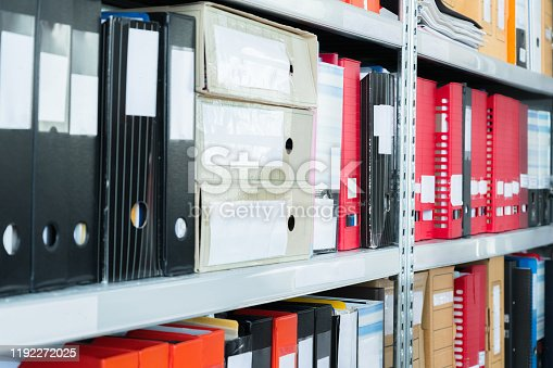 502086873 istock photo Colourful blank blind folders with files in the shelf. Archival, stacks of documents at the office or library. Physical document storage units 1192272025
