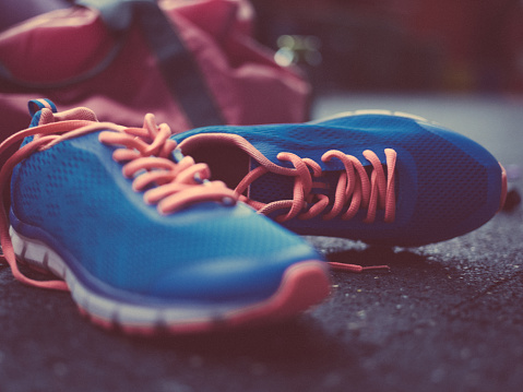 Closeup shot of colourful blue sneakers  with bright orange laces lying on a concrete floor in soft light in a gym with a gym bag in the background