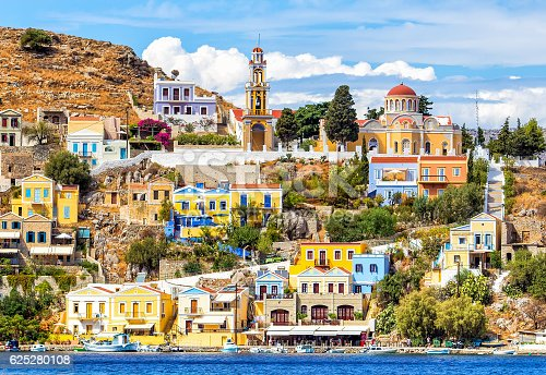 Colourful buildings and Church on beautiful summers day at Symi Town Greece EuropeGreece. Dodecanesse. Island Symi Simi  Colorful houses