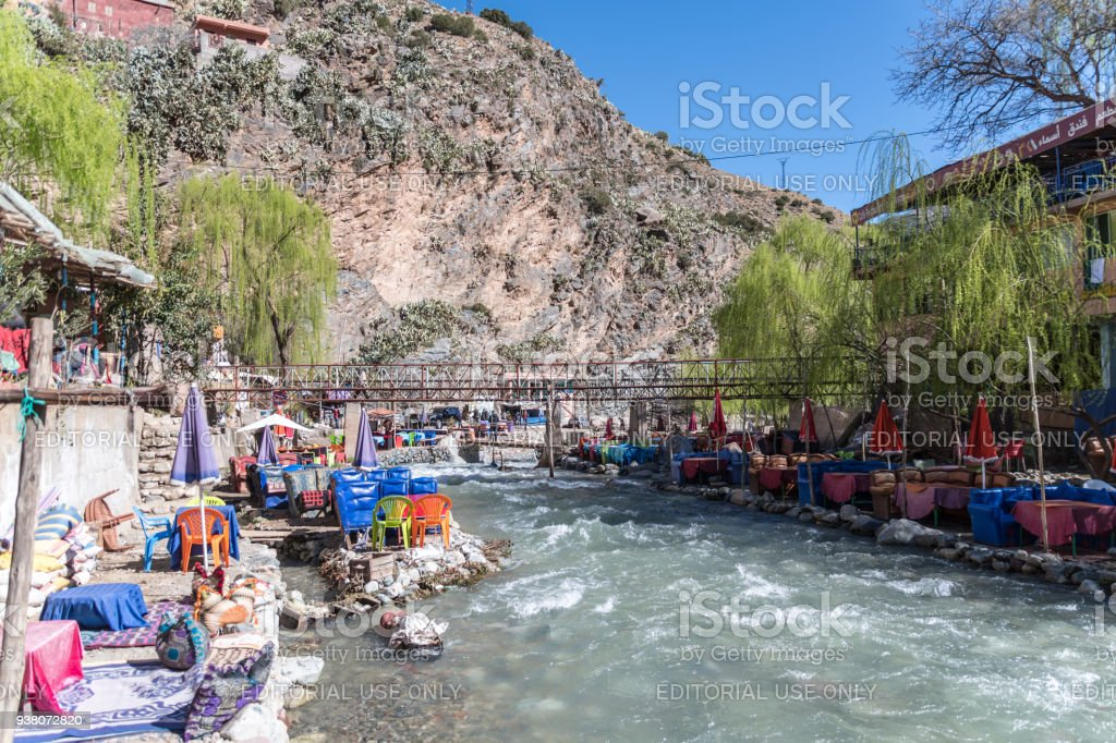 Colourful cafe seating by fast flowing river in Berber village in Atlas Mountains stock photo