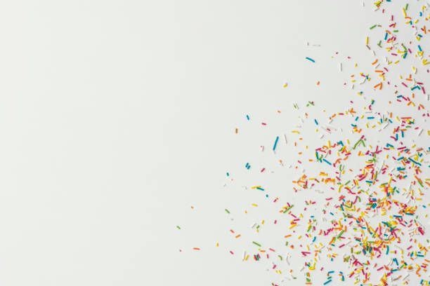 Colourful cake sprinkles on white background stock photo