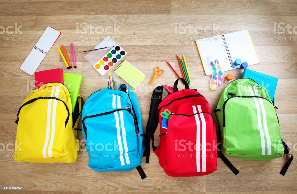 Colourful children schoolbags on wooden floor royalty-free stock photo