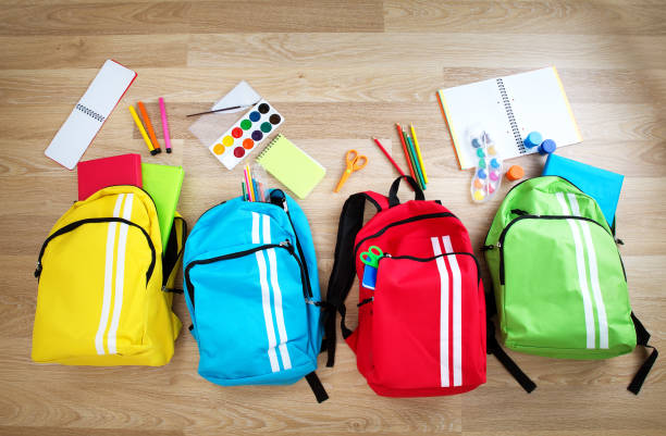 Colourful children schoolbags on wooden floor stock photo