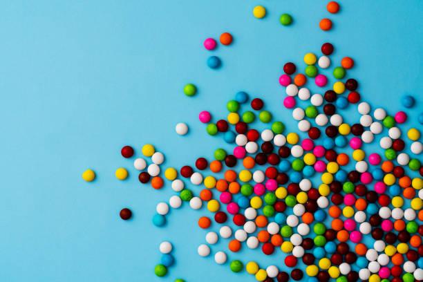 bunte schokoladenbohnenbonbons auf blauem hintergrund - süßigkeit stock-fotos und bilder