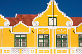 Top part of a colourful classical colonial dutch facade in Curacao, Caribbean island. Tiled roof, ornate facade, wooden windows, yellow wall.