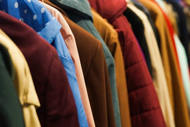 Colourful coats in the charity shop. stock photo