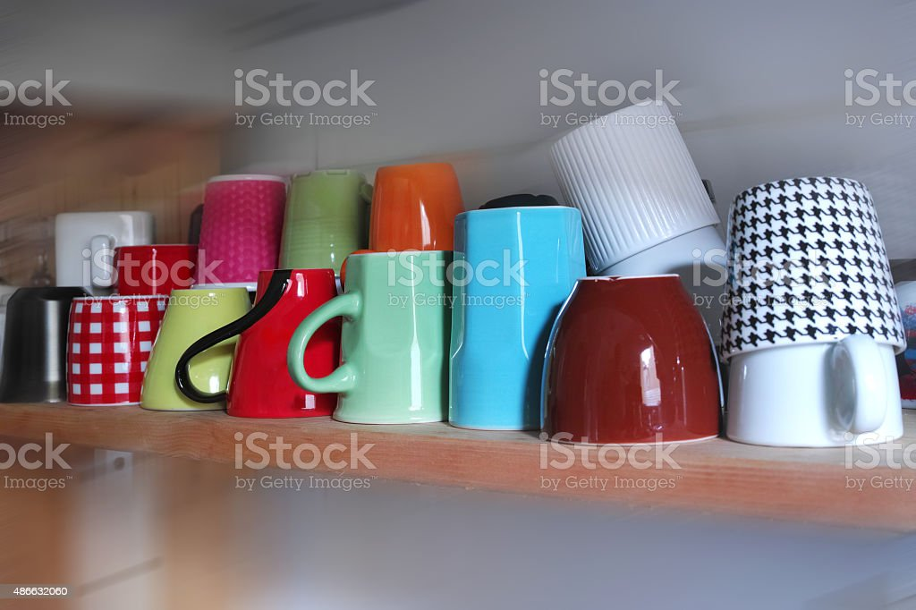 Colourful Coffee Cups On The Shelf At Kitchen stock photo