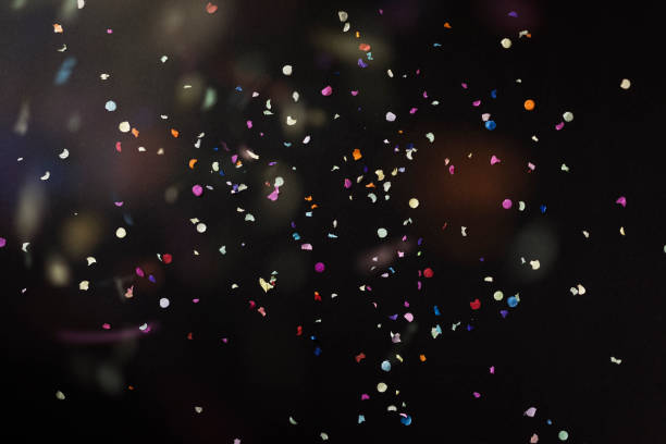 colourful confetti on black background - confetti stock pictures, royalty-free photos & images