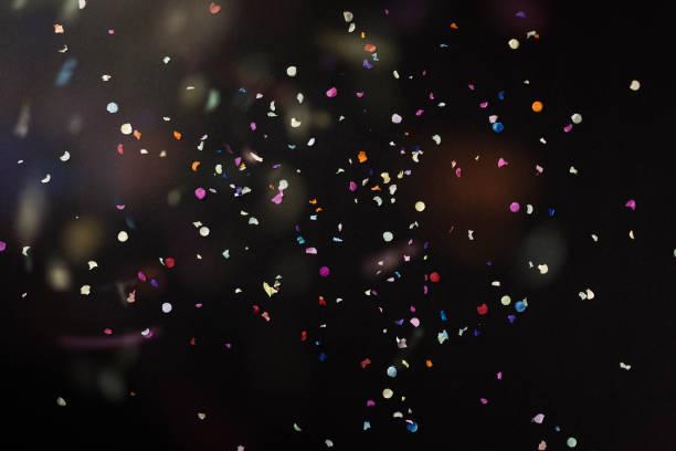 siyah arka plan üzerinde renkli konfeti - confetti stok fotoğraflar ve resimler
